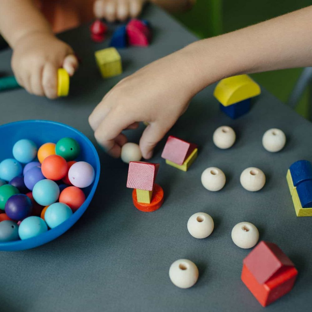 cropped-image-of-children-playing-with-blocks-and-4XKTV97