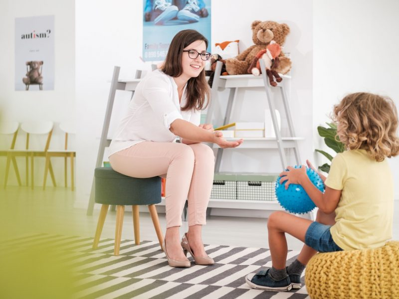 smiling-teacher-playing-with-child-with-blue-ball-CTM7GZE